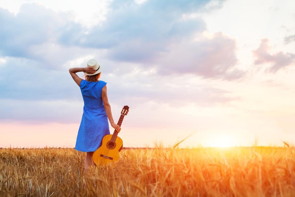 Woman musician with guitar, fields, sunset, warm summer outdoors
