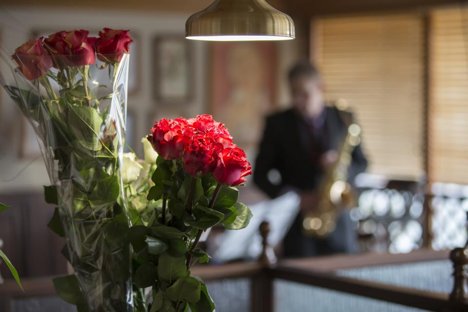 Background restaurant roses and blurry saxophonist with saxophone. Anniversary. Holiday event.