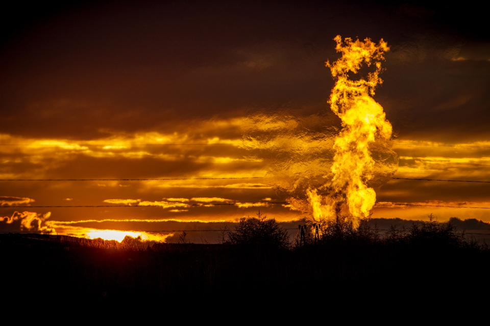 Burning off gas in a flare from a pit in a well pad.