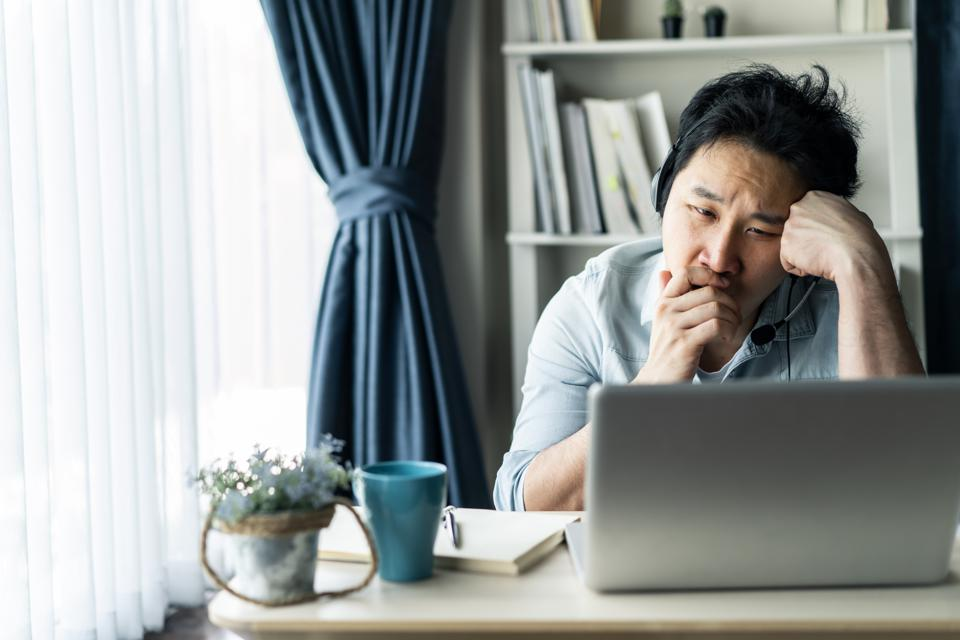 Asian young businessman working from home, man feeling tired, bored and sleepy sitting on table. He looking at computer thinking about job in living room at house, home office due to covid19 pandemic.