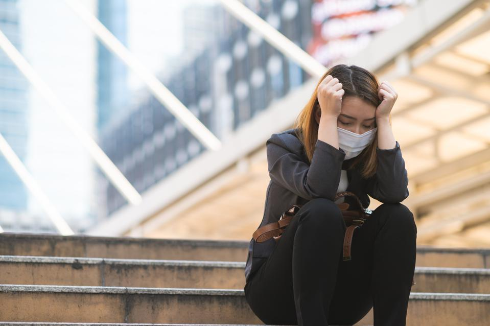 Unemployed businesswoman depressed sitting on a path due to company bankrupted while coronavirus spreading situation