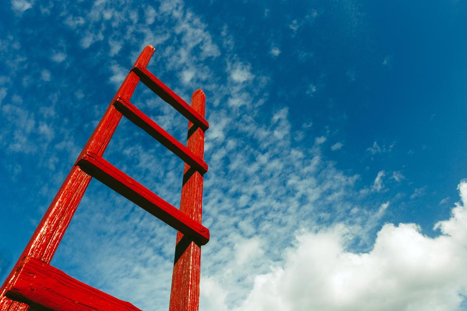 Red wooden ladder against blue sky with clouds showing opportunities to excel in your career.
