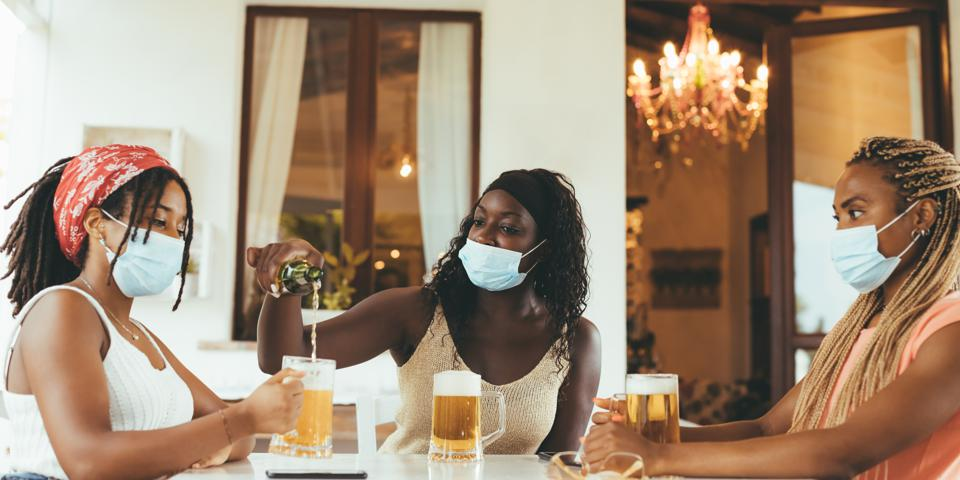 Three girlfriends sitting at the brewery (pub) with beer glasses wearing surgical masks.