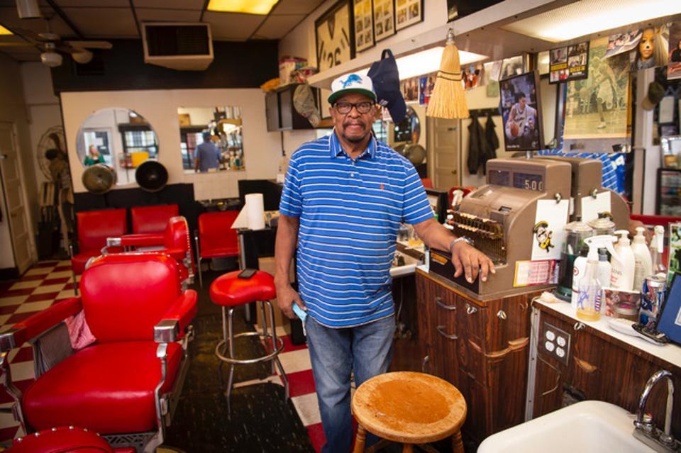 Black man standing in a barbershop