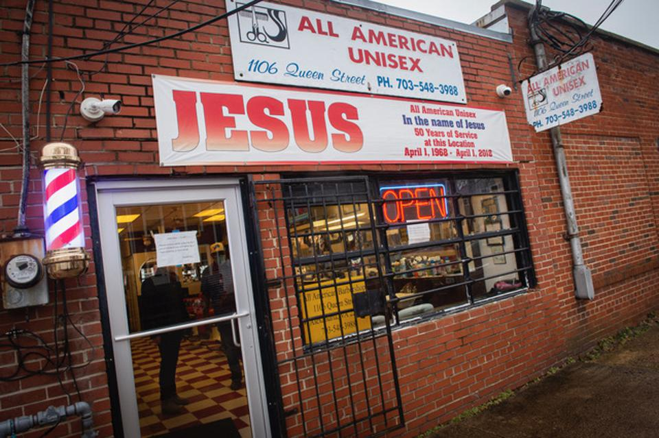 barbershop in a brick building with a pole and a sign that includes the name Jesus in large letters