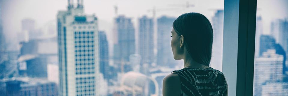 An image of a women staring out of a skyline from a tall skyscraper.