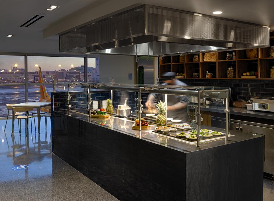 a chef cooks at the Centurion AMEX lounge in the Denver airport