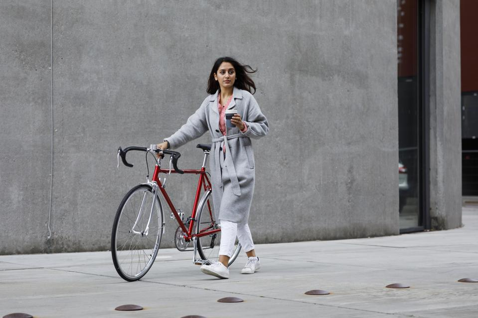 Young woman walking with bicycle, with reusable coffee cup in hand