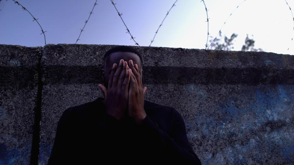 Depressed afro-american man standing near barbed wire fence, regretting crime