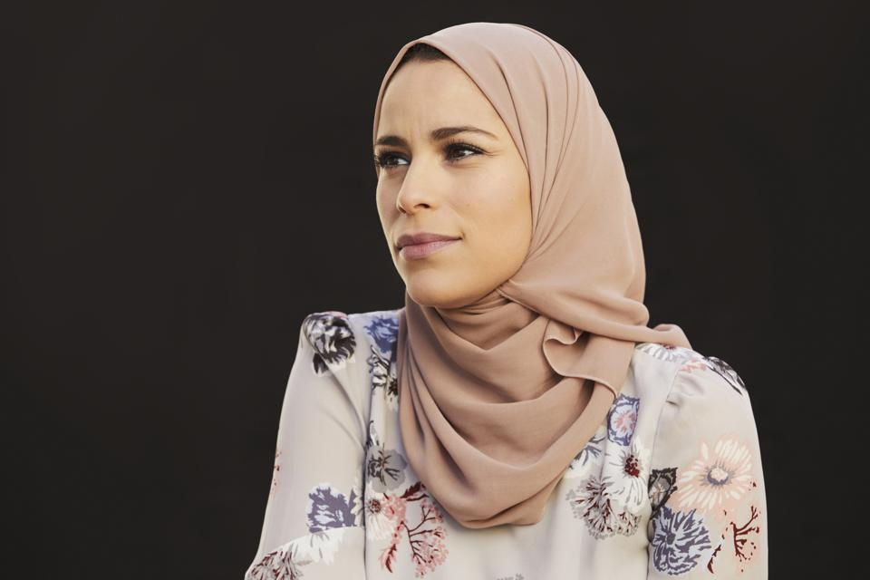 Portrait of Alaa Murabit, Libyan-Canadian woman, wearing a headscarf and a floral shirt.