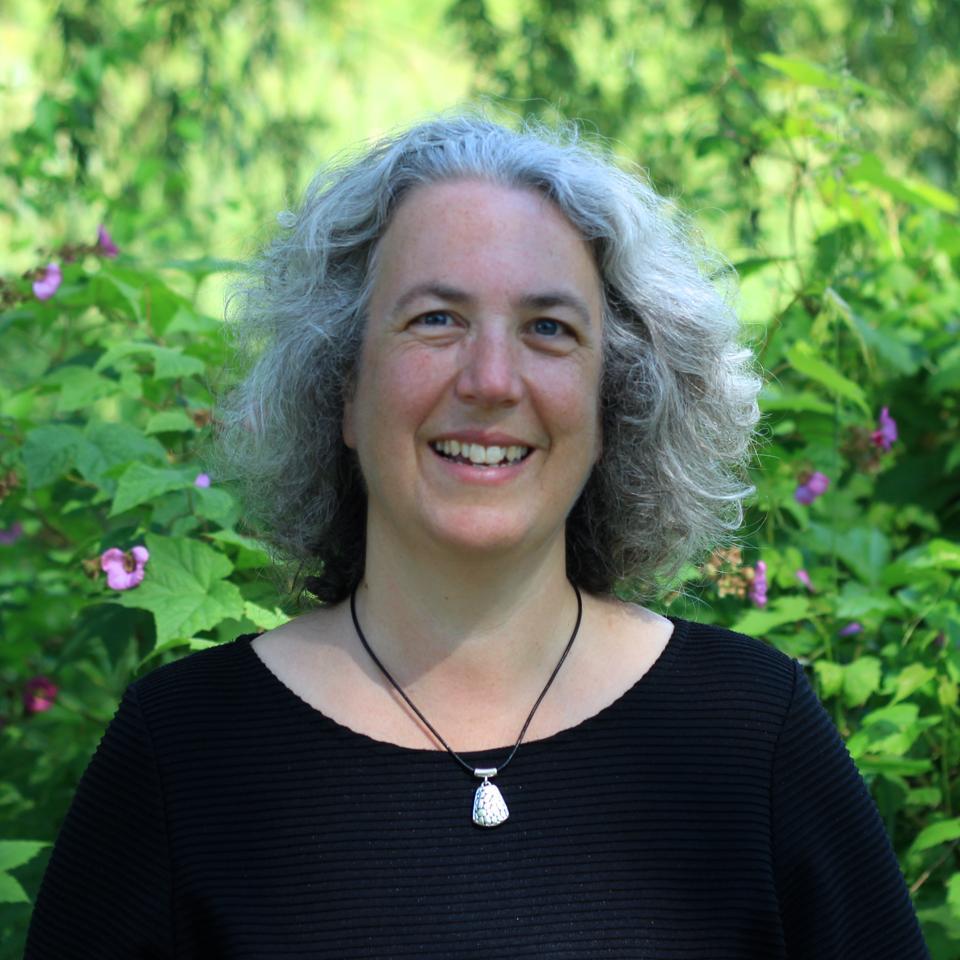 Elizabeth Sawin. White woman with white hair, wearing a black shirt, foliage backdrop.