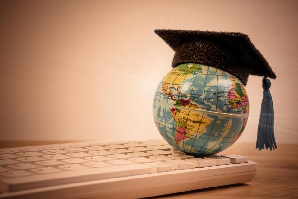 Graduation cap on top earth globe model map on computer keyboard background. Graduate study abroad program.