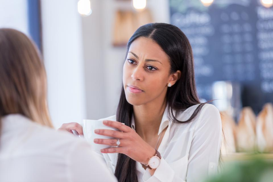 Concerned young woman talks with friend in coffee shop