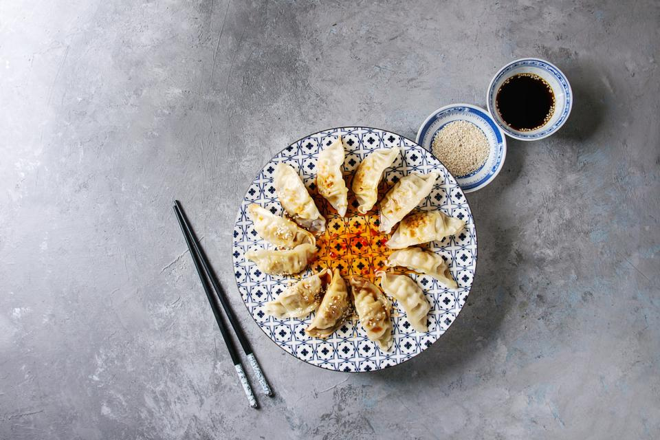 Asian dumplings Gyozas potstickers on white blue ceramic plate served with chopsticks and bowl of soy sesame sauce over grey texture background Top view, copy space