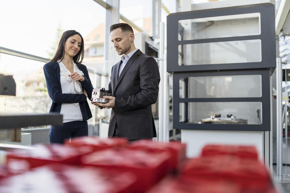 Businessman and businesswoman looking at workpiece in factory