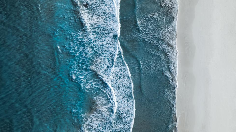 Drone shot showing waves rolling onto a beach, Esperance, Australia