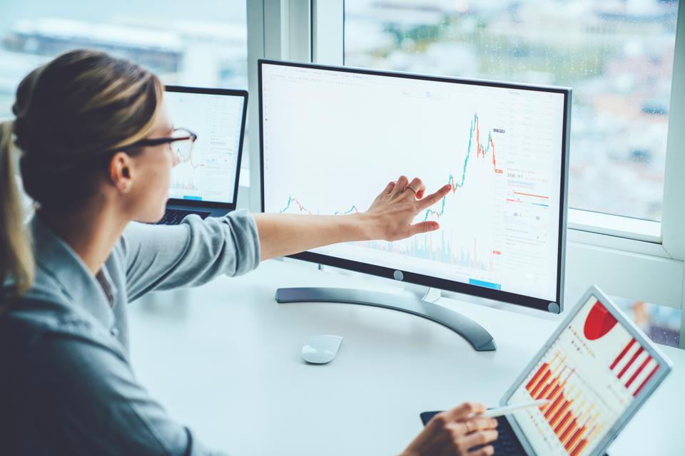 Business woman looking at financial data on computer screen and tablet