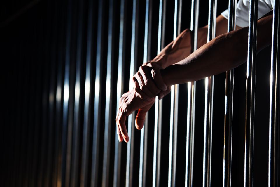 Close-up of hand in jail background