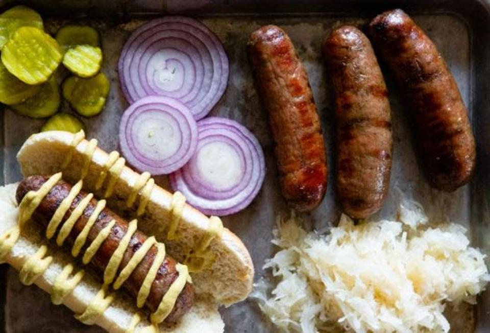 a tray filled with grilled bratwurst and wagyu beef from Kansas.