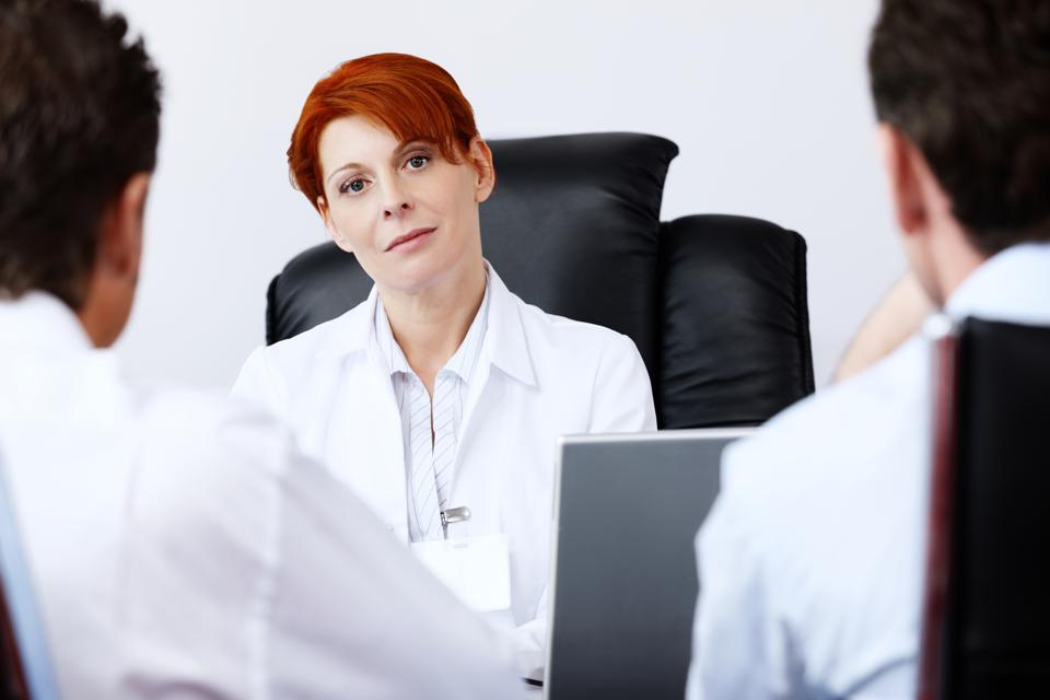 female doctor talking with two male patients