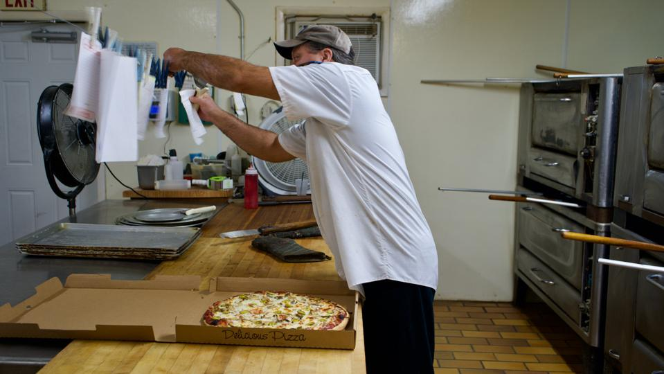 A worker checking orders in the kitchen of Kozy's Pizza in Mauston, WI.