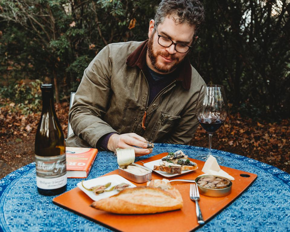 Ben Simon at a table with wine and food