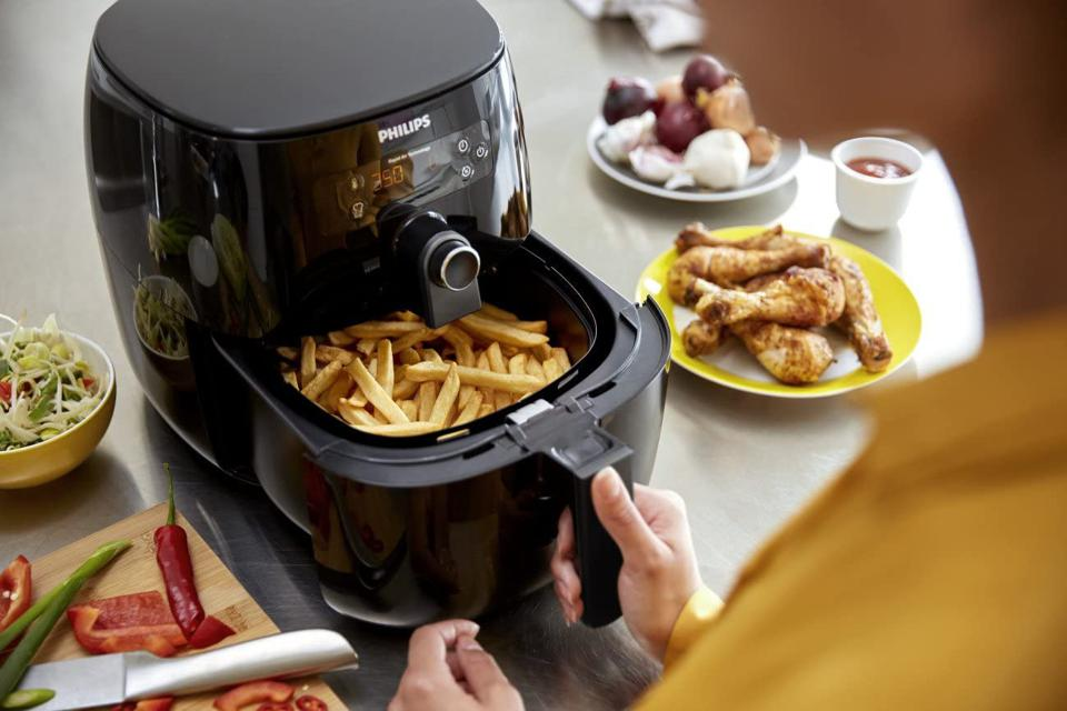 Philips air fryer filled with French fries, sitting next to chicken drumsticks