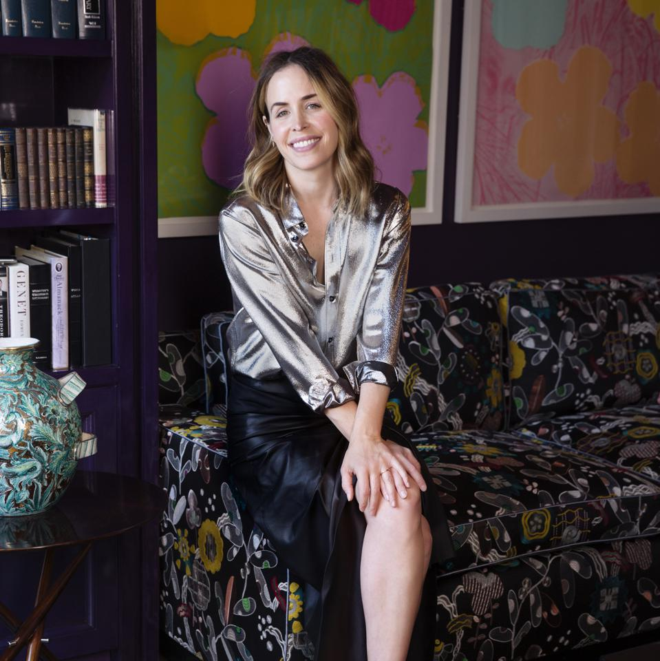 Designer Brett Heyman sits on a patterned couch in a silk shirt and black skirt.