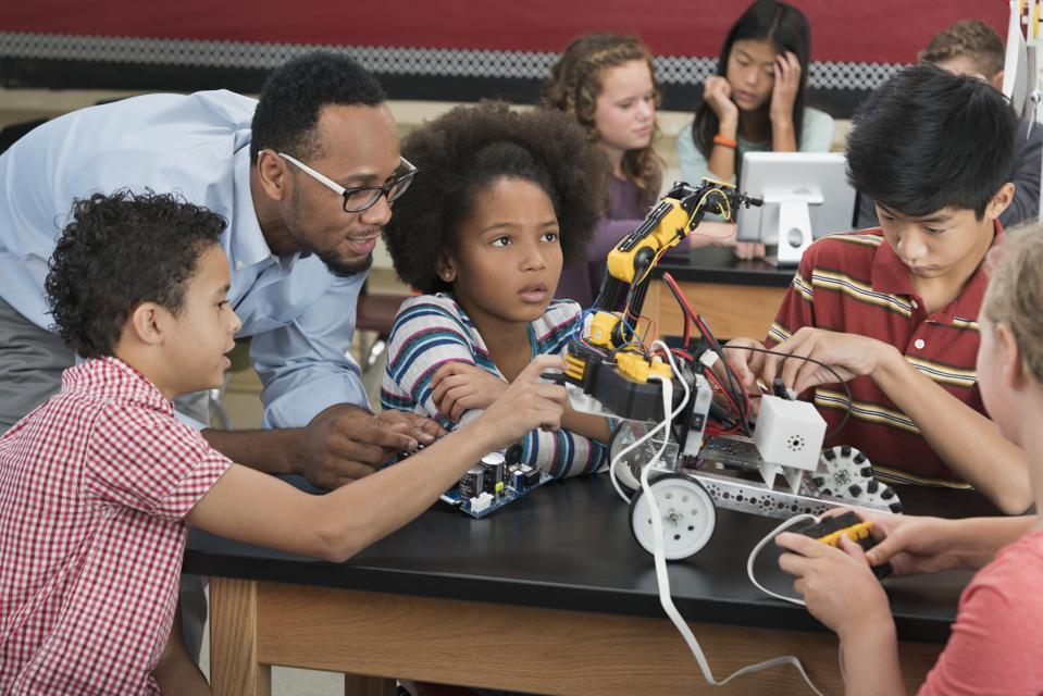 Teacher helping students in robotics class