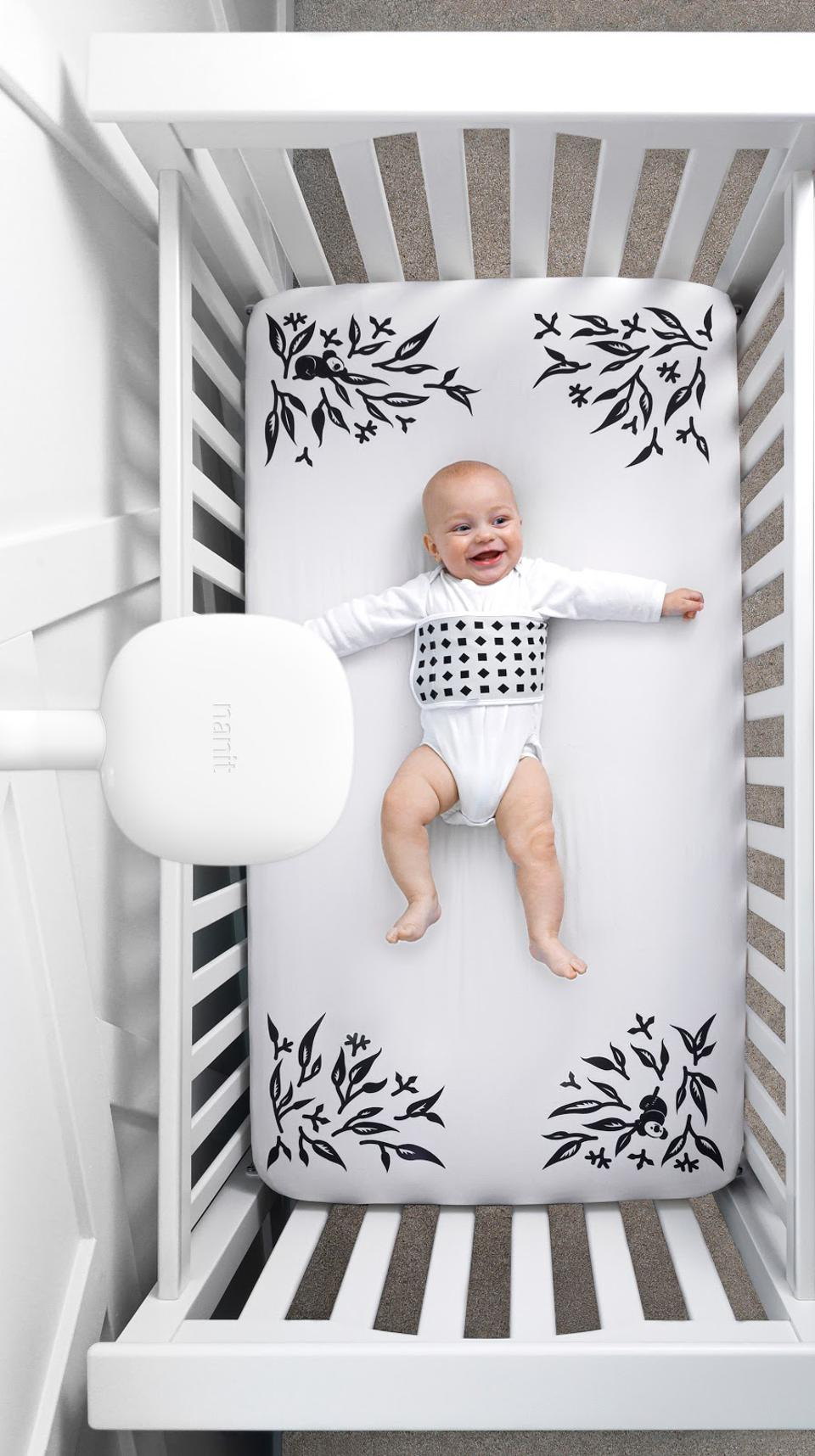 image of a baby lying on a black and white sheet in a crib with a baby monitor above
