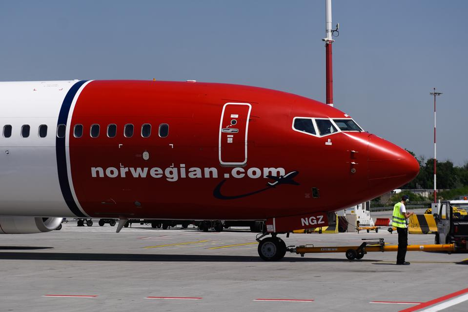 Norwegian Air plane parked on an airport runway.