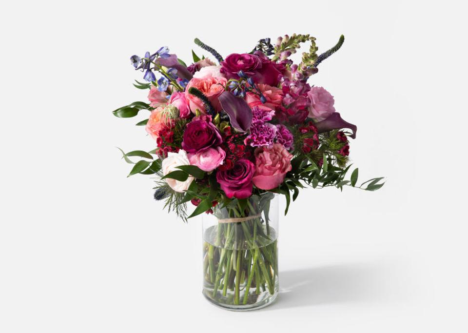 A pink and purple bouquet of Roses, Calla Lilies, Ranunculus, Thistle, and Snapdragons