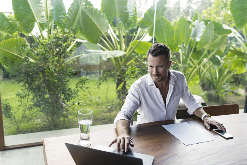 Mature man sitting at table in front of lush garden, using laptop