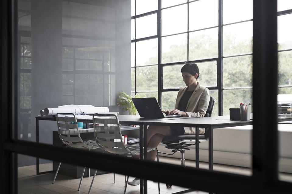 Entrepreneur typing over laptop in modern office