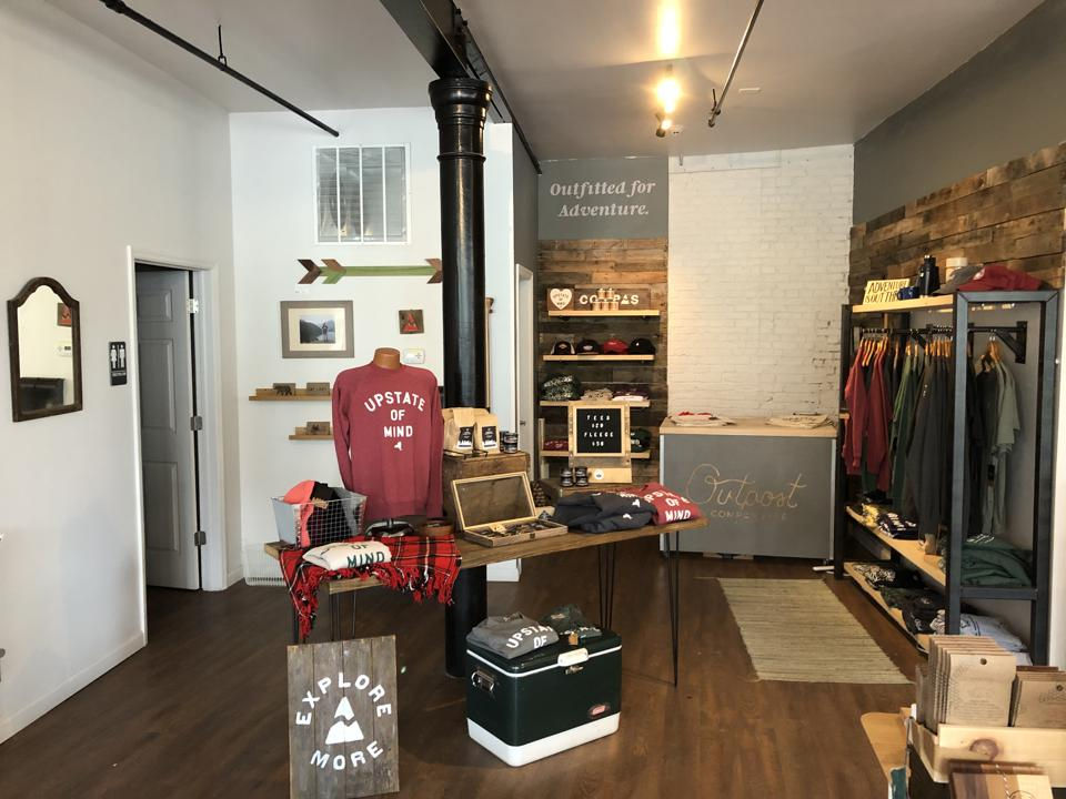 A retail space with shirts, sweaters, and other items available for sale.