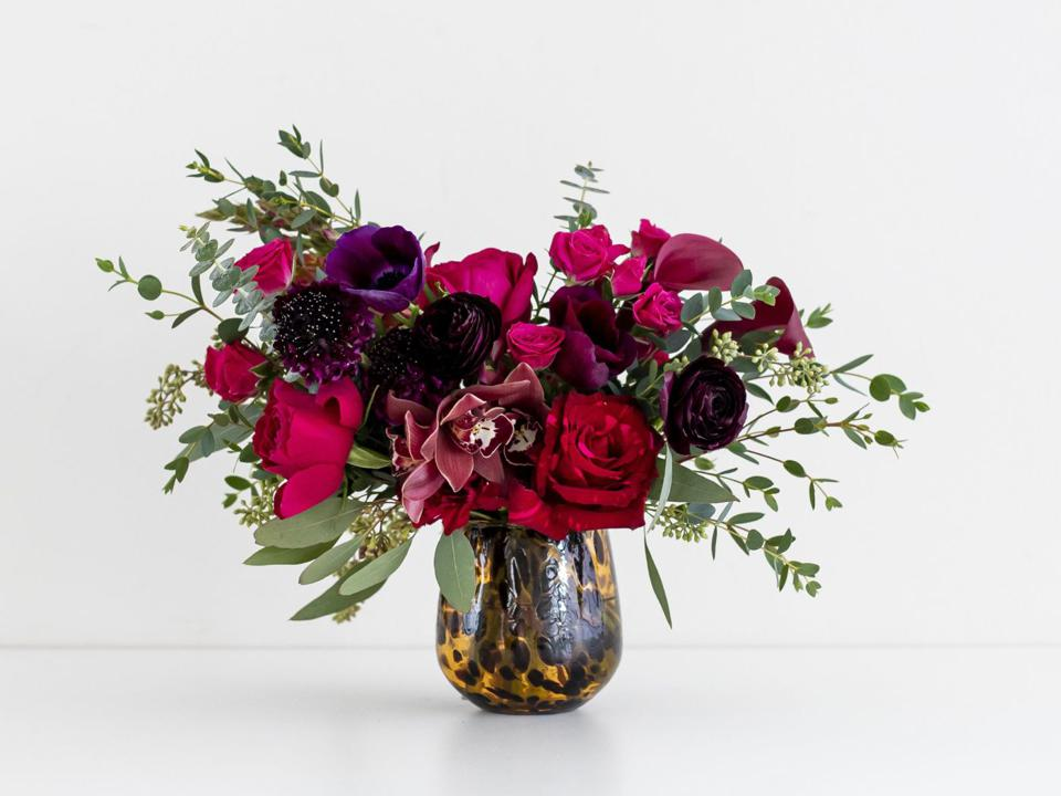 Burgundy, pink, and purple flowers in a blown glass vase