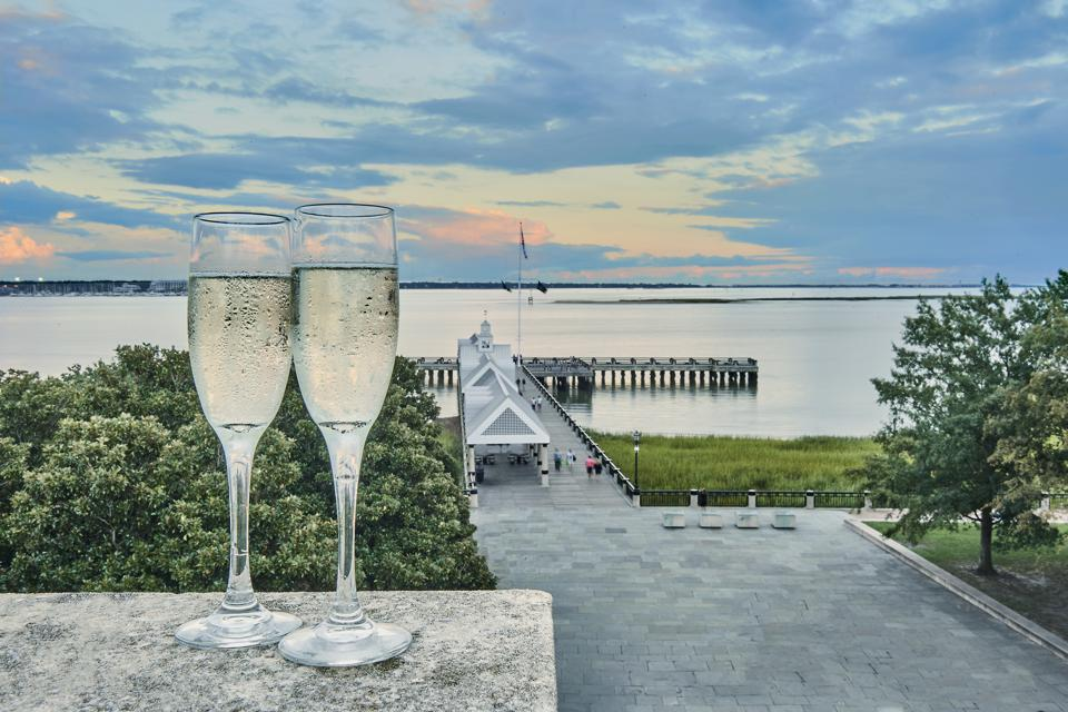 two champagne glasses overlooking a dock and harbor at sunset