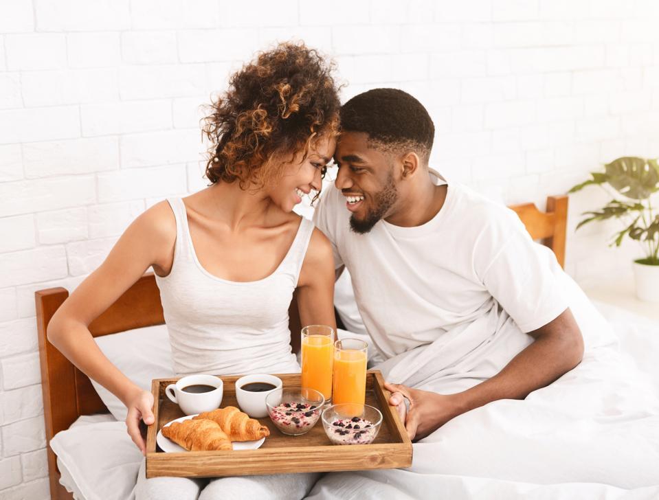 Happy black couple enjoying breakfast in bed