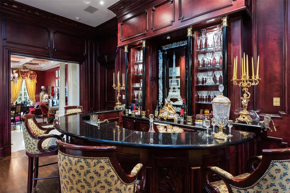 Mahogany bar with wine cellar underfoot.