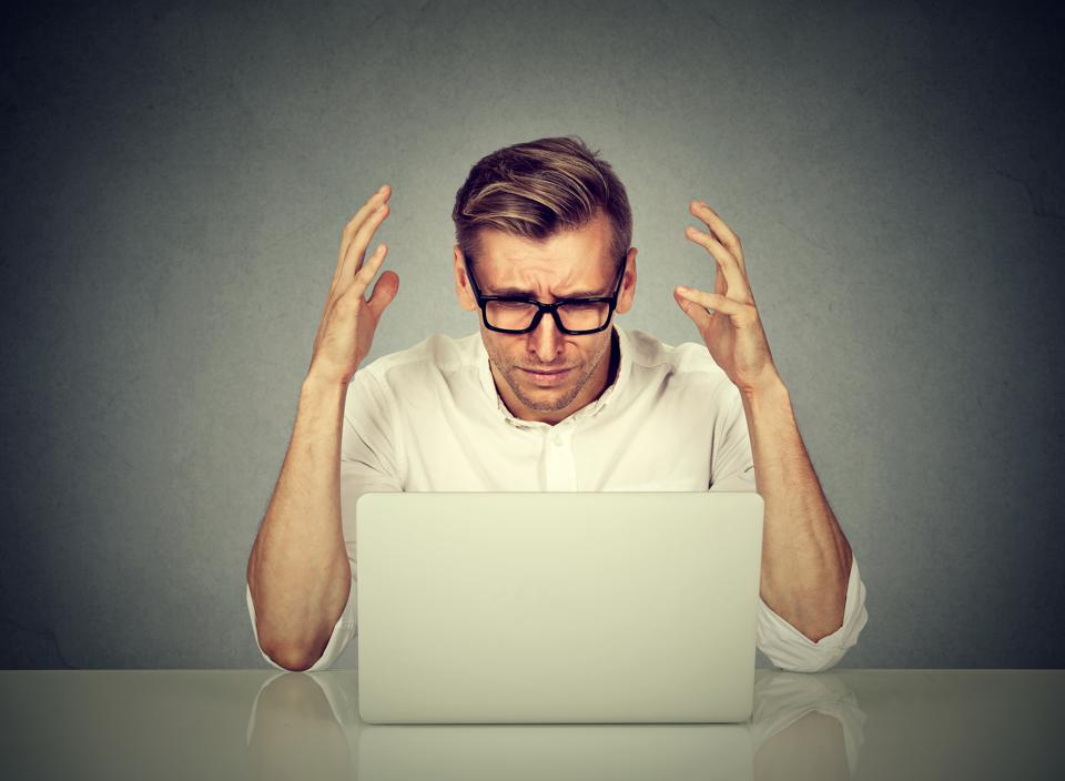Stressed man working on computer.