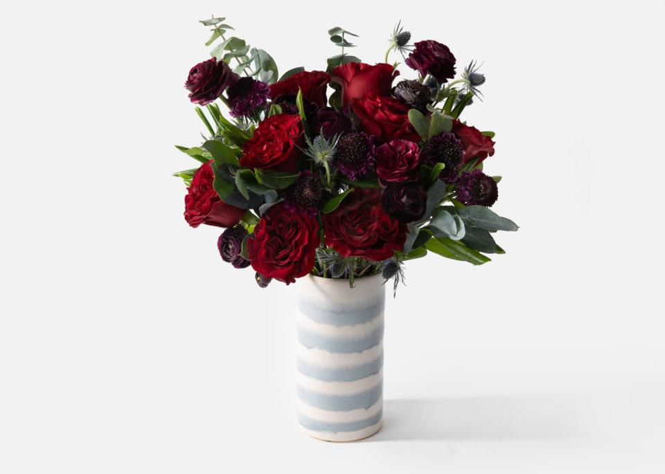 Crimson, red, and deep purple Valentine's Day flowers in a striped ceramic vase