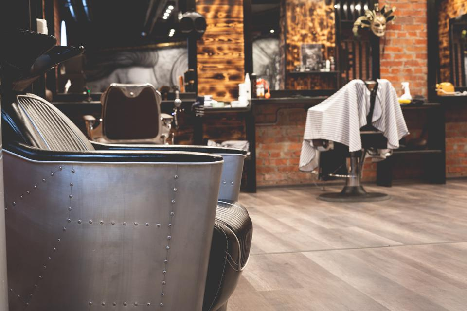 Chair for washing your hair in a barbershop. Barbershop interior. Brutal place. Leather armchair with metal upholstery. Selective focus.