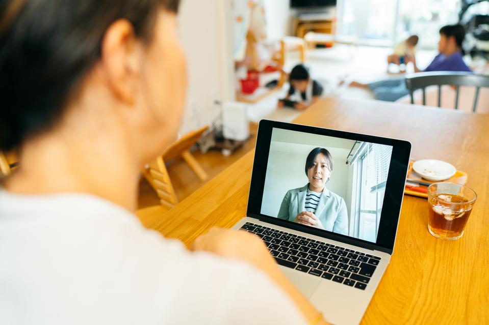 Mother talking with mental health professional via web conference at home