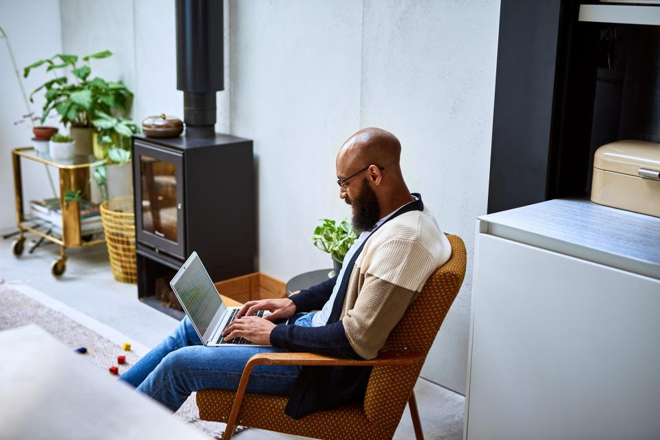 Man with beard using laptop at home on retro chair