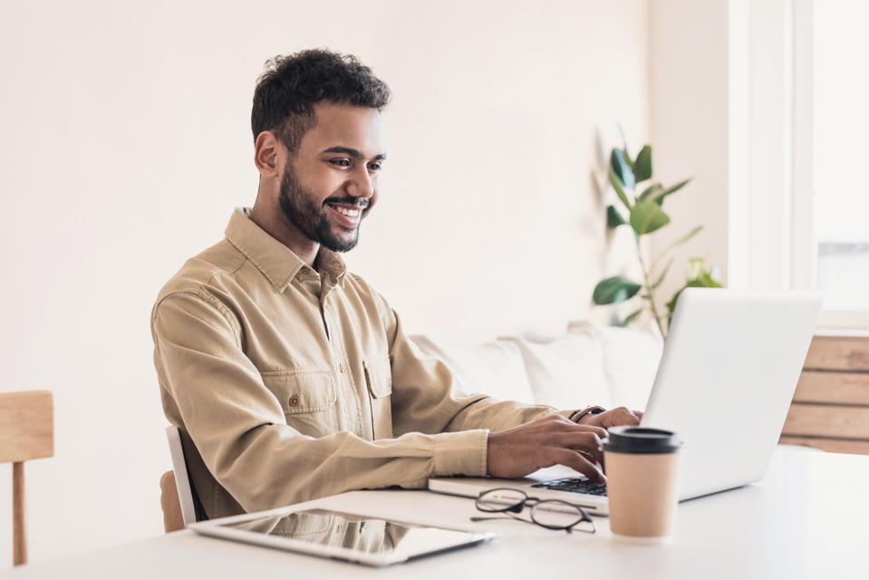 Cheerful man using laptop working at home online