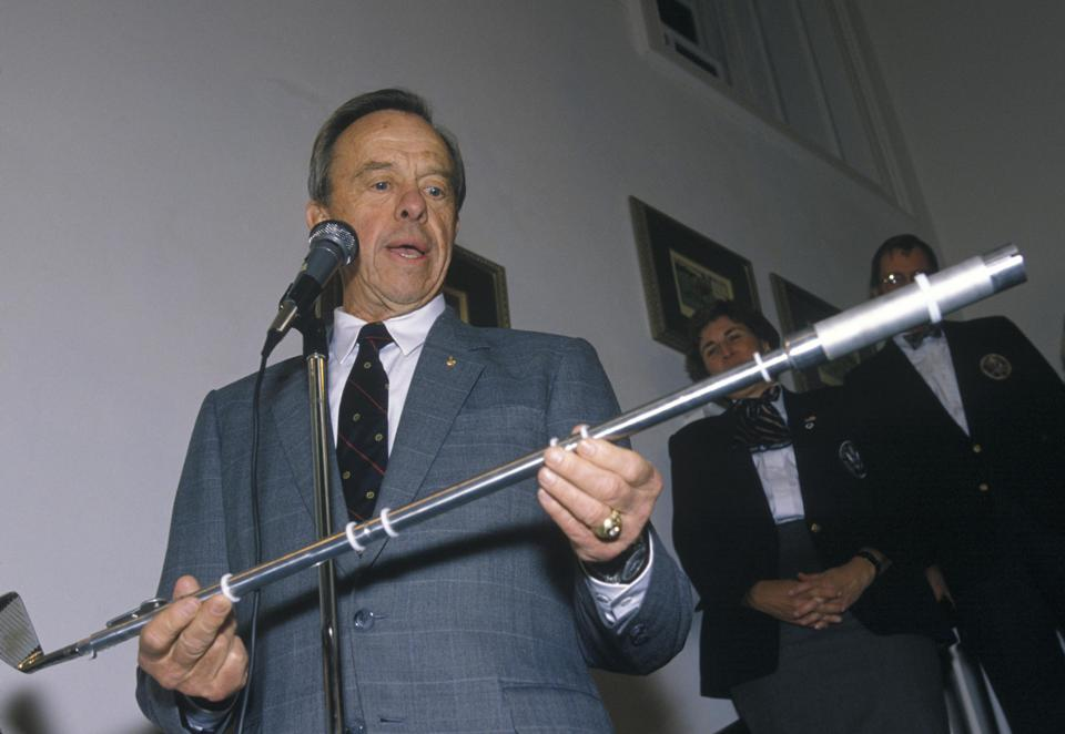 Astronaut Alan Shepard holds the golf club he used on the Apollo 14 mission