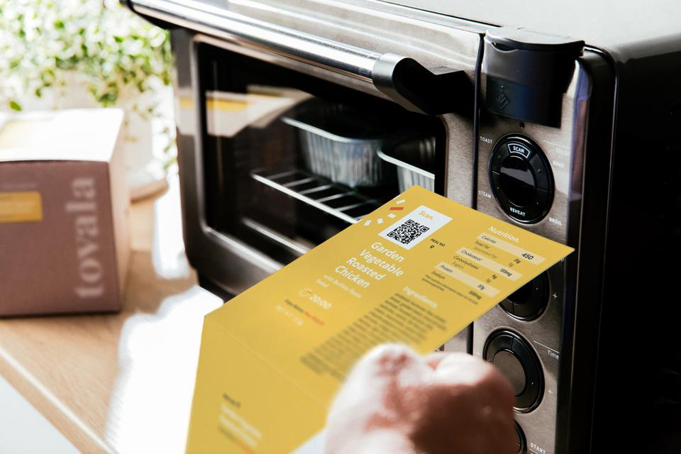 A customer scans a recipe on Tovala's smart-oven, which is programmed to cook the meal to pre-programmed specifications.