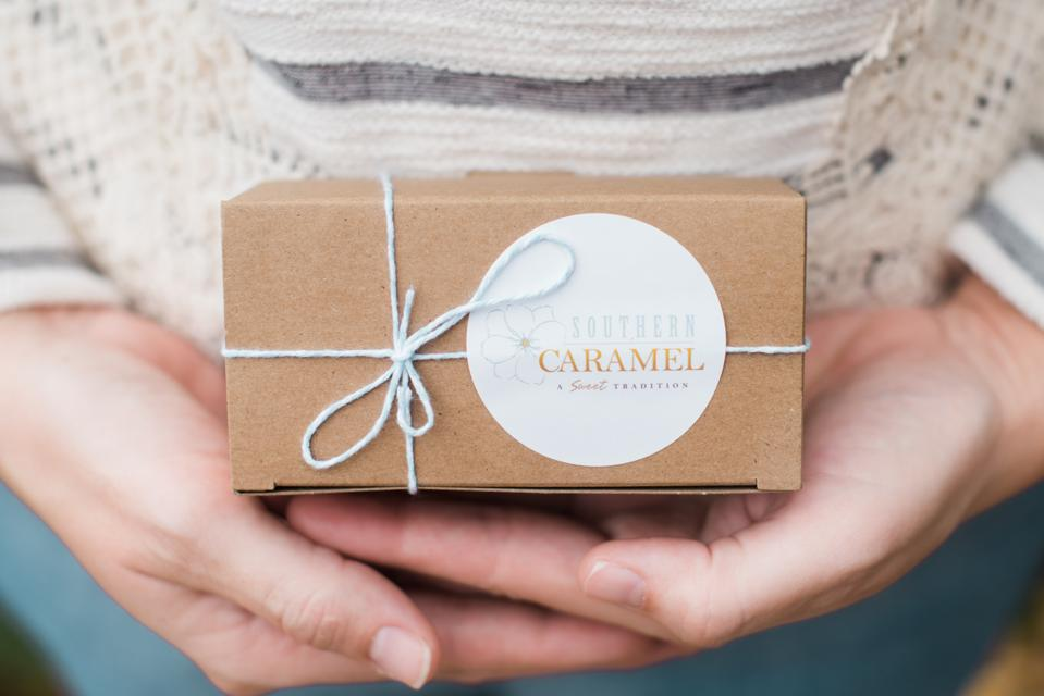 a woman's hands hold a box of handmade caramels