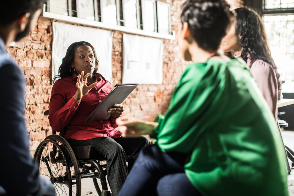 Businesswoman in wheelchair leading group discussion in creative office