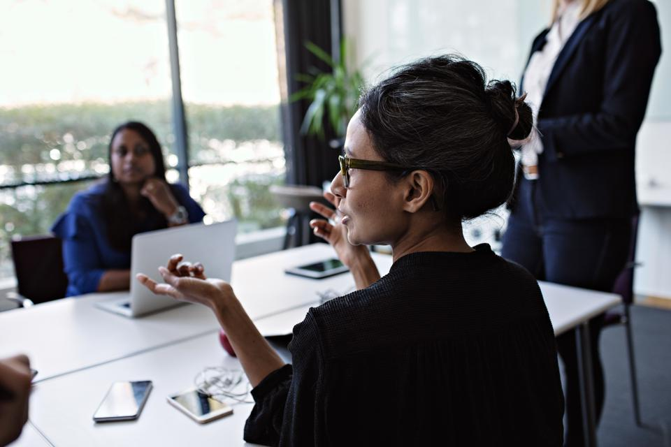 Businesswoman gesturing while discussing with colleagues during meeting at conference table in board room